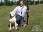 Dr. Antonio Nores Martinez sitting with a Dogo Argentino